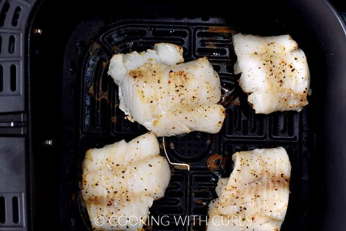 Four baked cod filets in an air fryer basket.