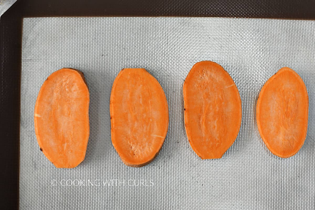 Four slices of sweet potato on a silicone lined baking sheet.