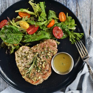 Looking down on a bone-in pork chops topped with garlic butter with greens and cherry tomatoes on the side.