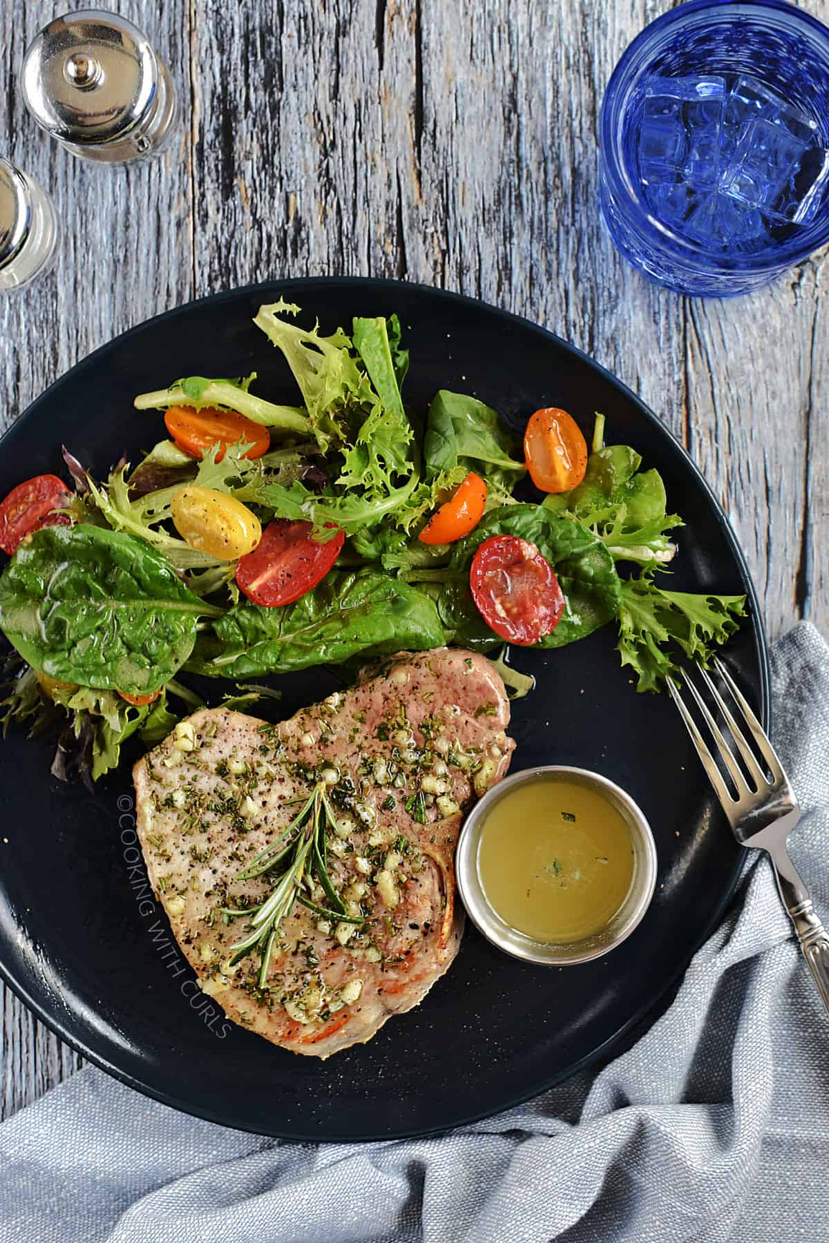 Looking down on a pork chop topped with garlic and rosemary butter with a green salad on the side.