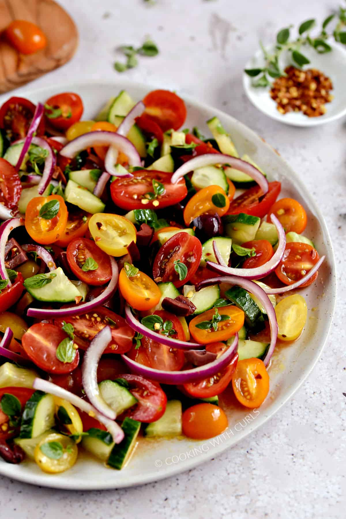 A close-up view of a large plate with sliced cherry tomatoes, cucumber, kalamata olives, and red onion with fresh oregano leaves and crushed red pepper.