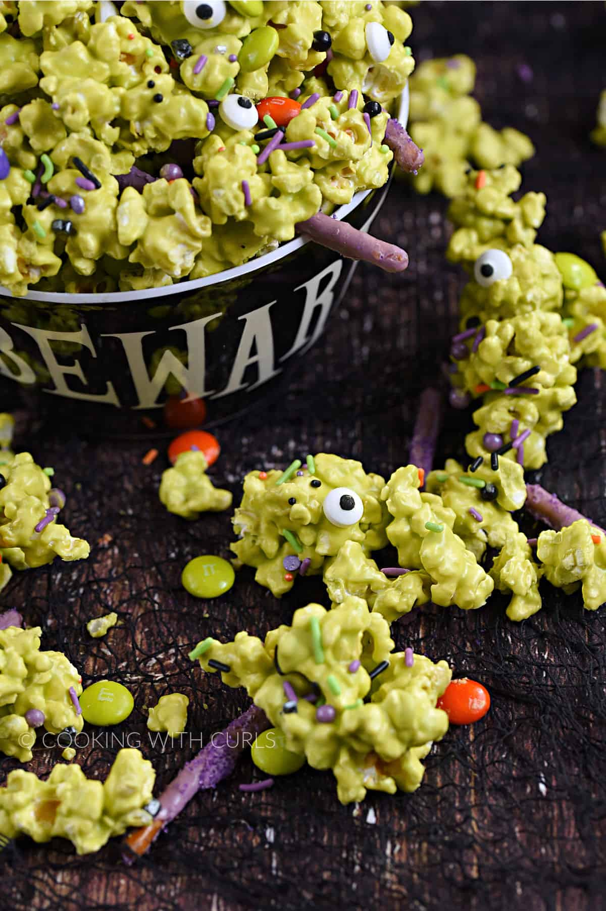 Green candy coated popcorn with candy eyes, sprinkles, purple pretzel sticks, and candy coated chocolates overflowing a bowl onto a wood surface.