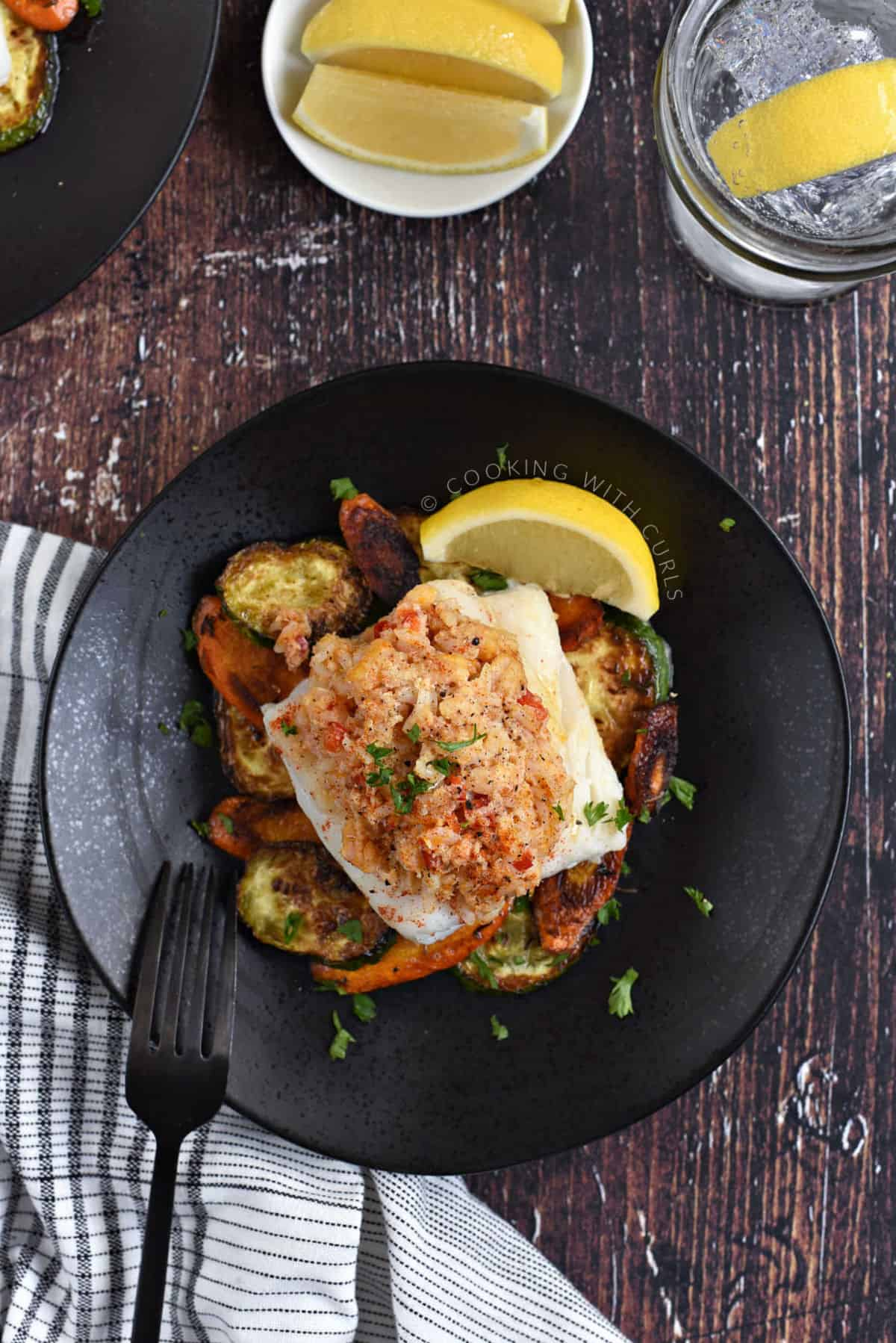 Looking down on a stuffed cod filet on top of sautéed zucchini and carrots with a slice of lemon on the plate and several more in a small bowl.