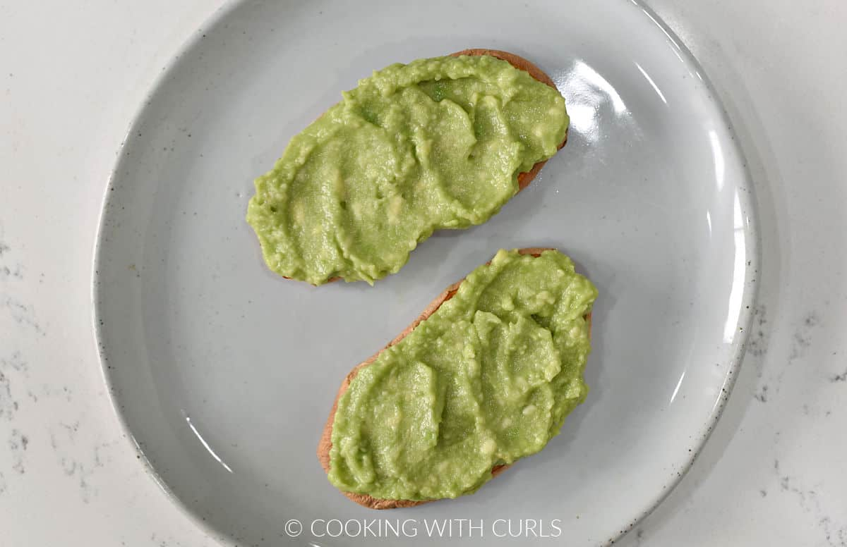 Mashed avocado spread over two slices of sweet potato toast.