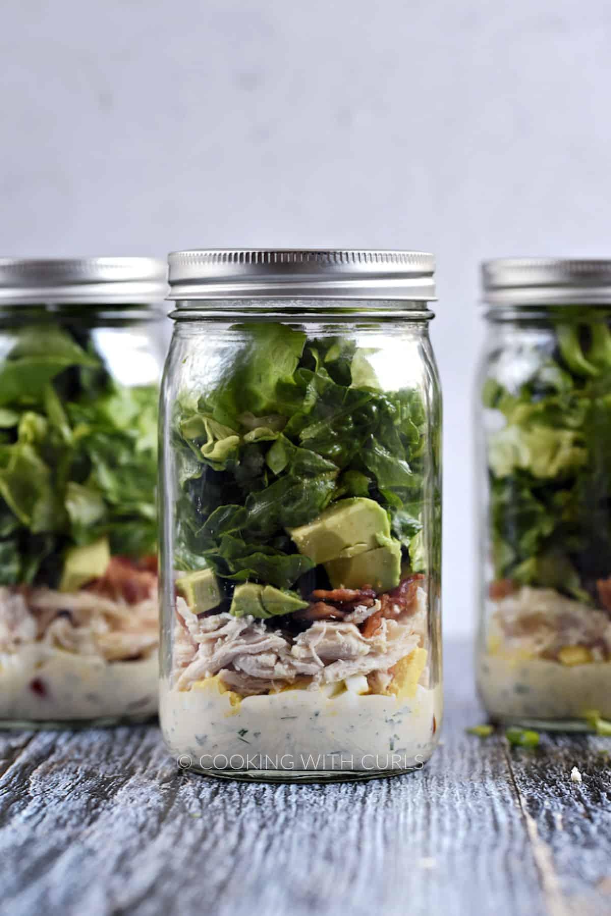 Three Mason Jar Cobb Salad with Ranch Dressing in a row.