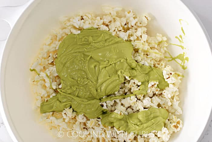 Melted green chocolate poured over popcorn in a large bowl.
