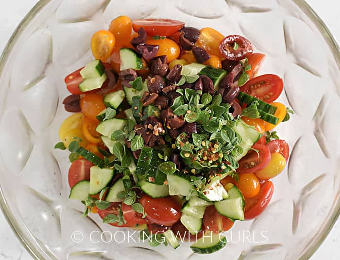 Oregano leaves, crushed red pepper, chopped olives and cucumber on top of the tomatoes in a large bowl.