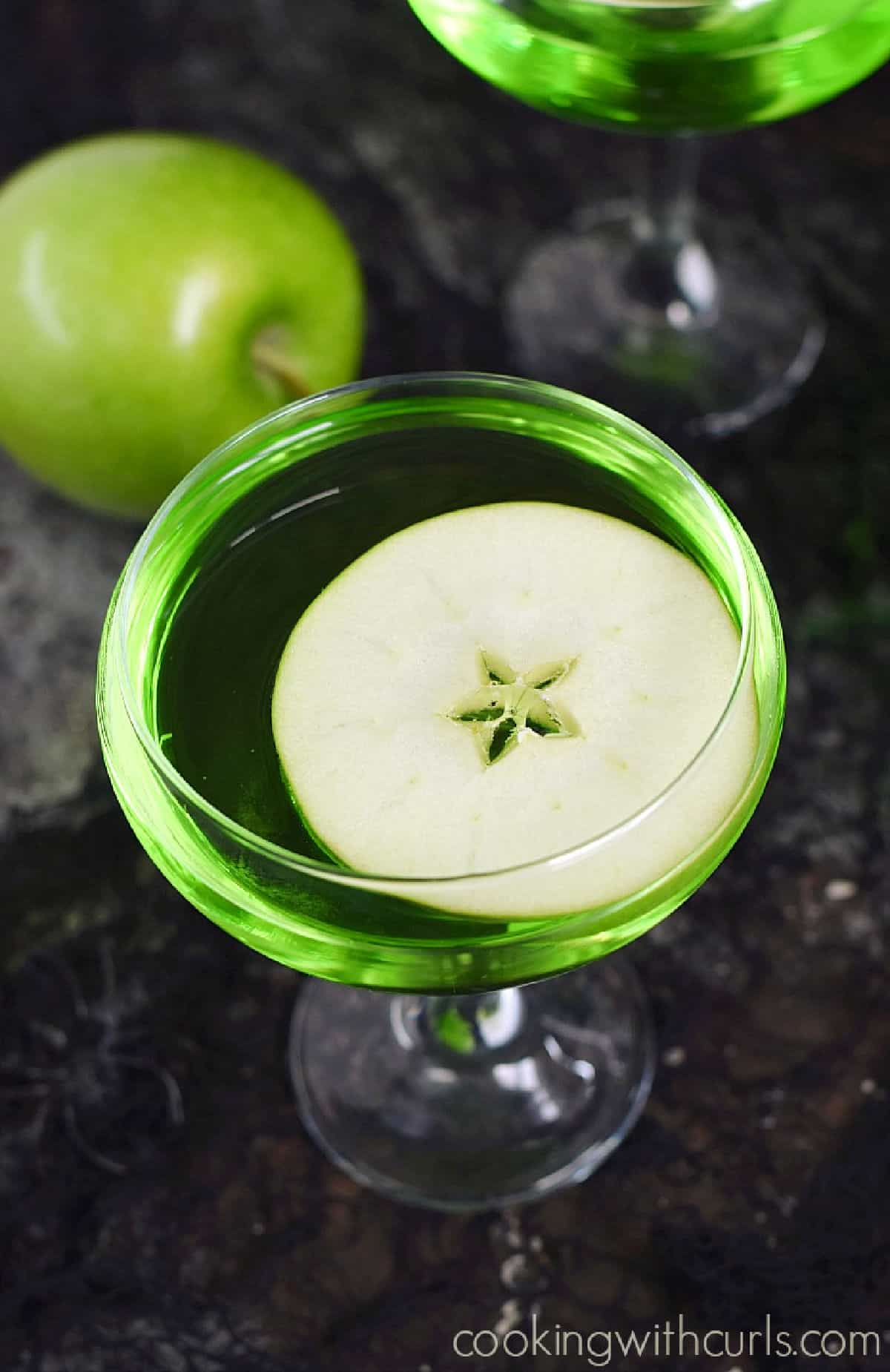 Looking down on a green cocktail with a floating apple slice with a second drink in the background with a green apple.