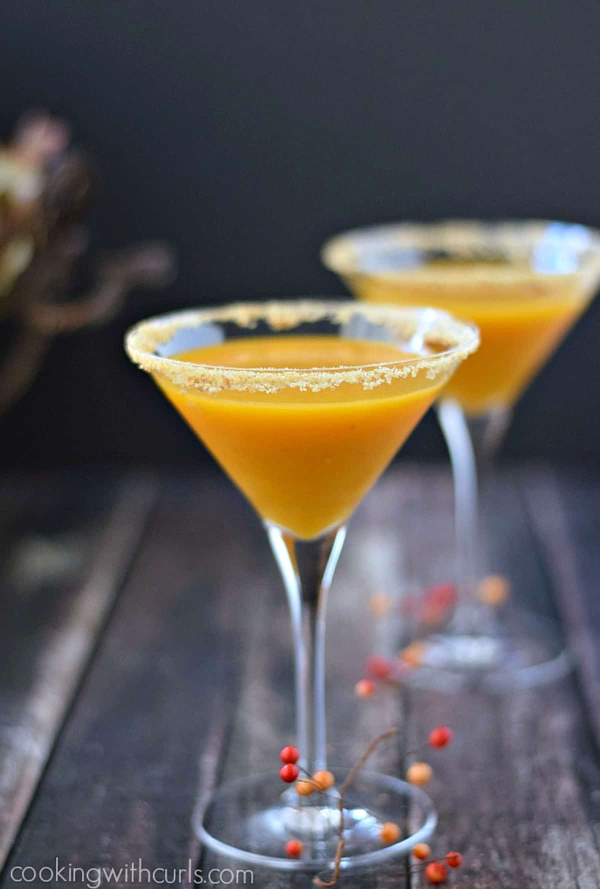 Two pumpkintini filled martini glasses with graham cracker crumbs around the rims.