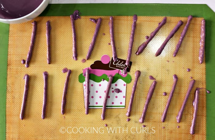 Purple candy coated pretzel sticks on a silicone lined baking sheet.