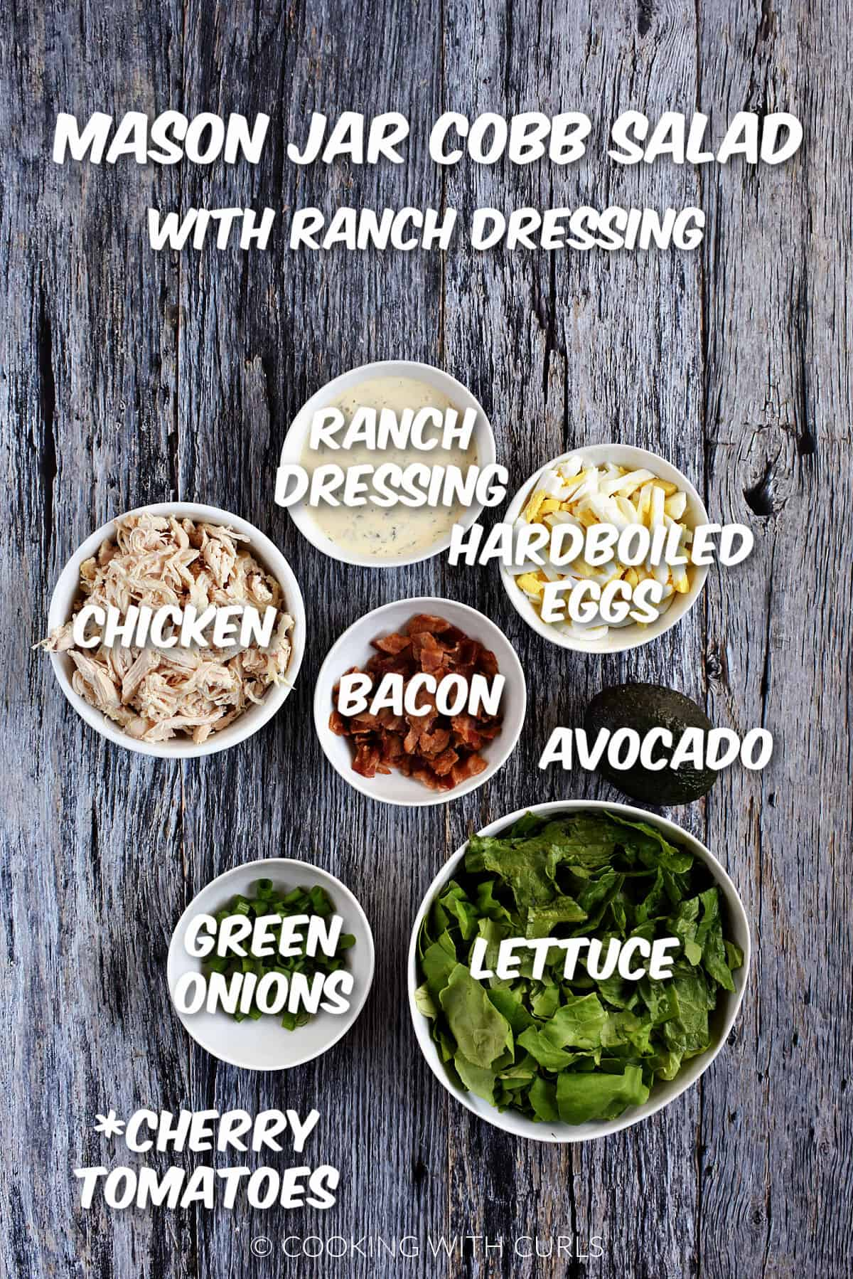 Ranch dressing, hardboiled eggs, avocado, bacon, chicken, green onions, and lettuce in white bowls and cherry tomatoes listed.