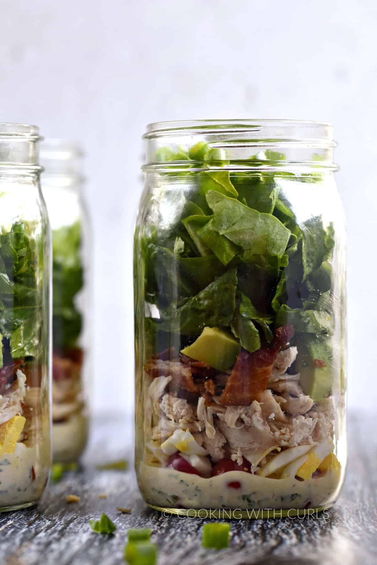 Ranch dressing, tomato, egg, bacon, avocado, and lettuce layered in a Mason jar.