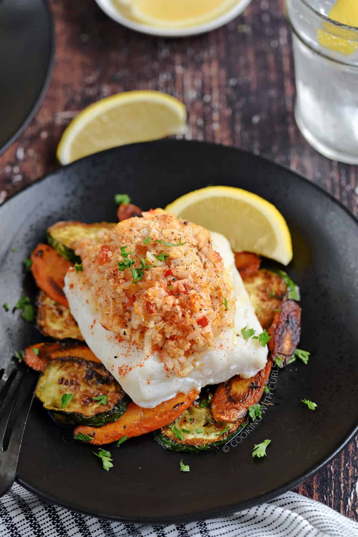 Shrimp and Crab Stuffed Cod on a bed of sautéed zucchini and carrots with a lemon wedge on the side.