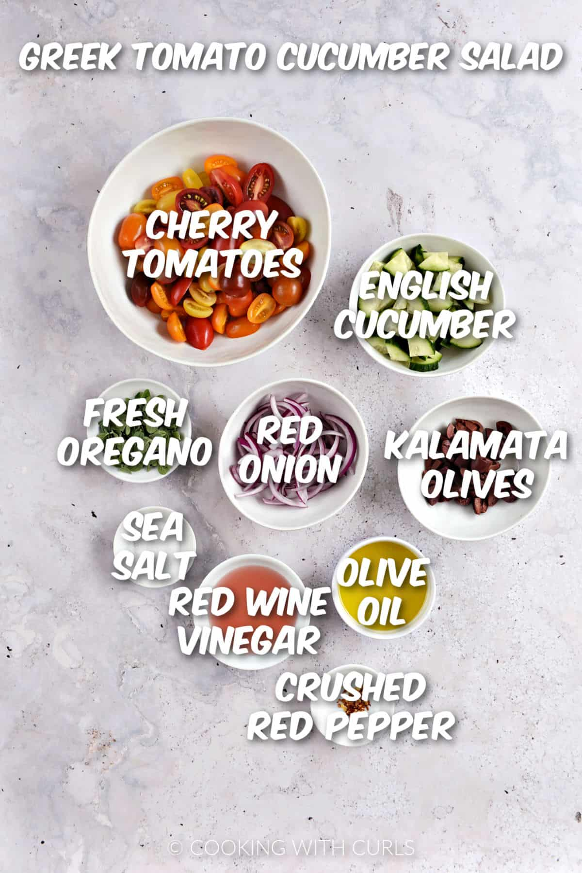 Sliced cherry tomatoes, cucumber, red onion, kalamata olives, oregano leaves, sea salt, red wine vinegar, olive oil, and crushed red pepper in white bowls.