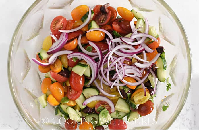 Thin slices of red onion on top of the tossed tomato cumber mixture.