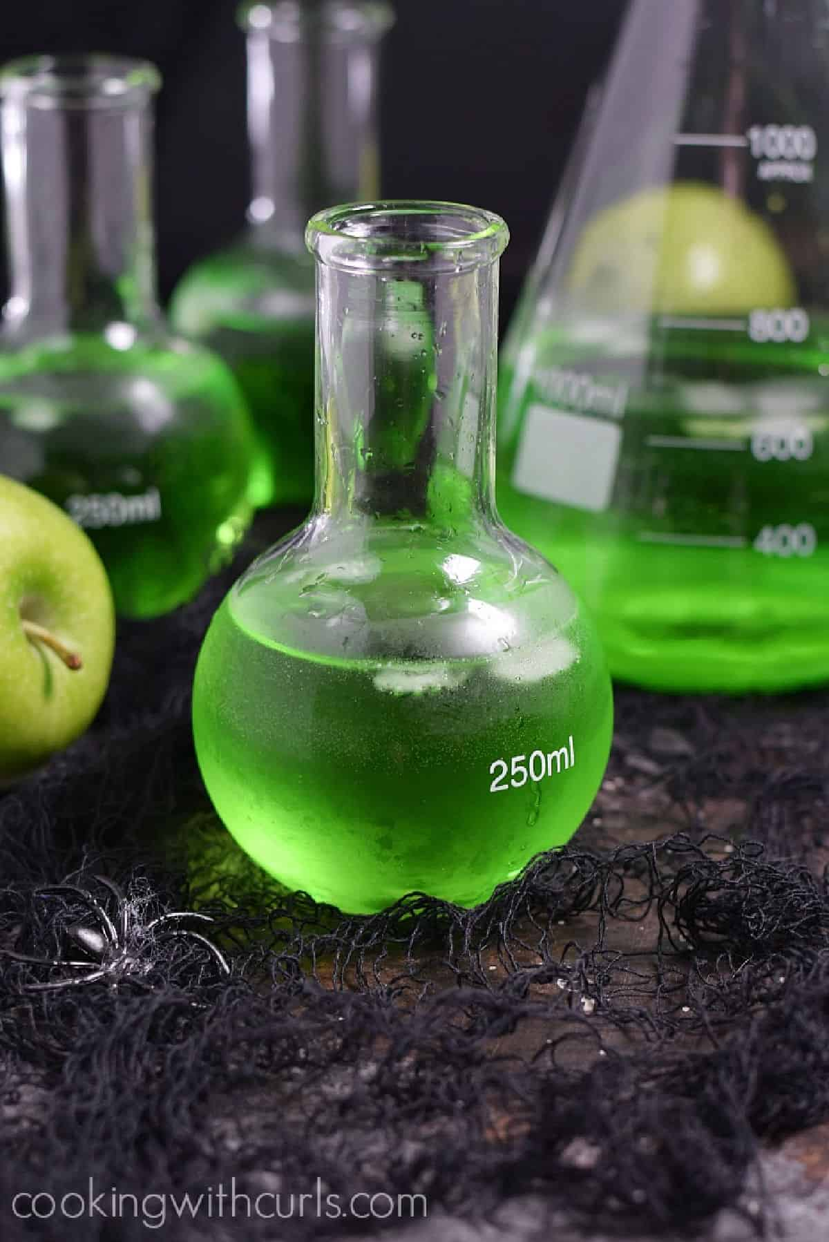 Three Poisoned Apple Cocktails in glass science bottles and a large beaker.