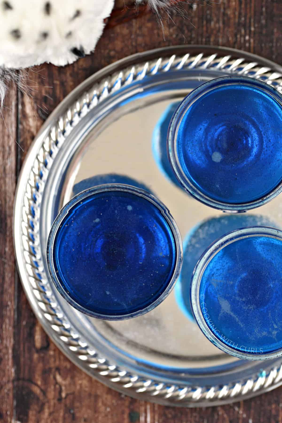 Three blue drinks in coupe style glasses on a silver tray.