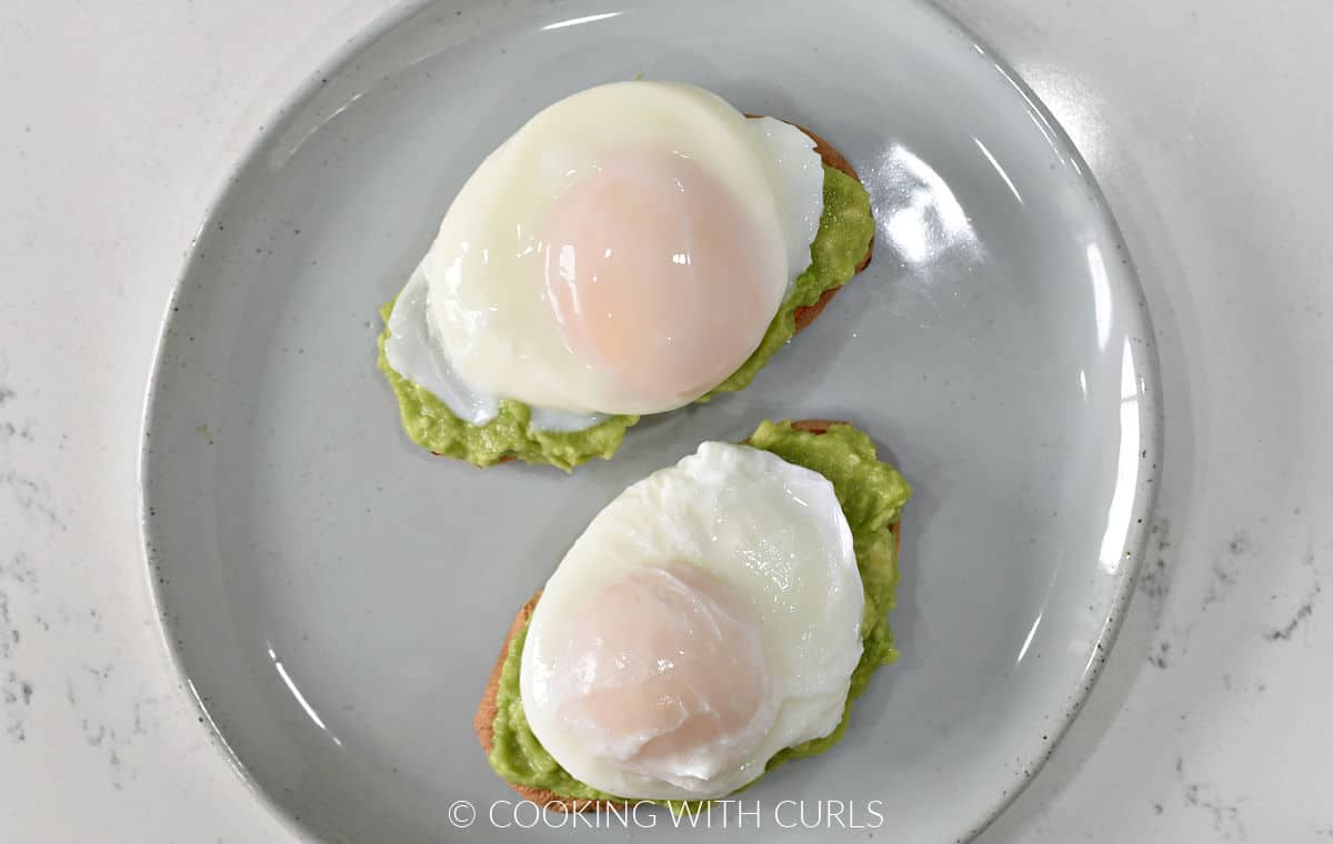 Two poached eggs on top of mashed avocado and two sweet potato toasts on a small plate.