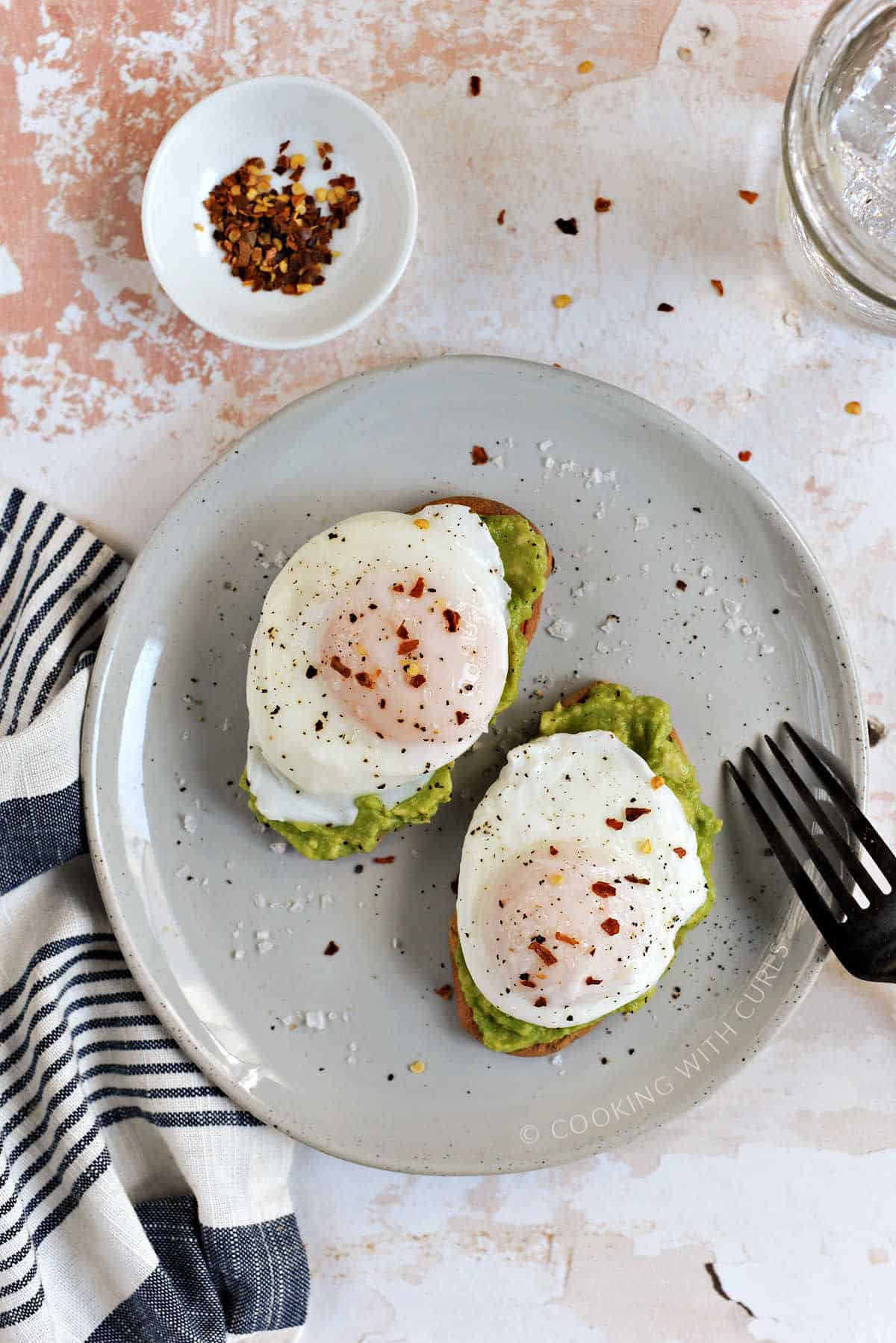 Two poached eggs sprinkled with flaked salt and red pepper flakes on top of two slices of avocado toast on a small plate.