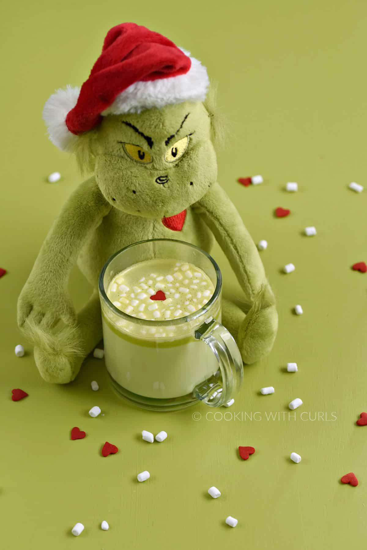 A stuffed Grinch doll sitting behind a mug of green hot chocolate on a green background with scattered red hearts and mini marshmallows.