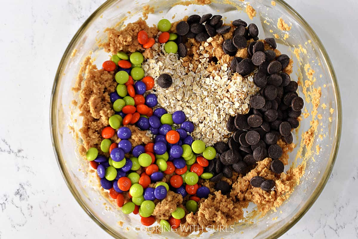 Chocolate chips, oats, and M&M's added to the cookie batter in a large bowl.