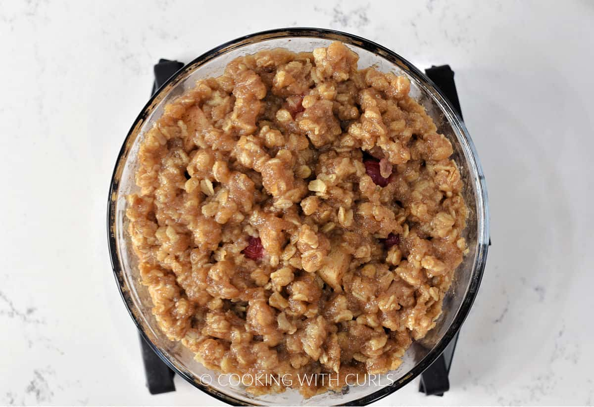 Cooked apple cranberry crisp in a small glass bowl sitting on a silicone trivet.