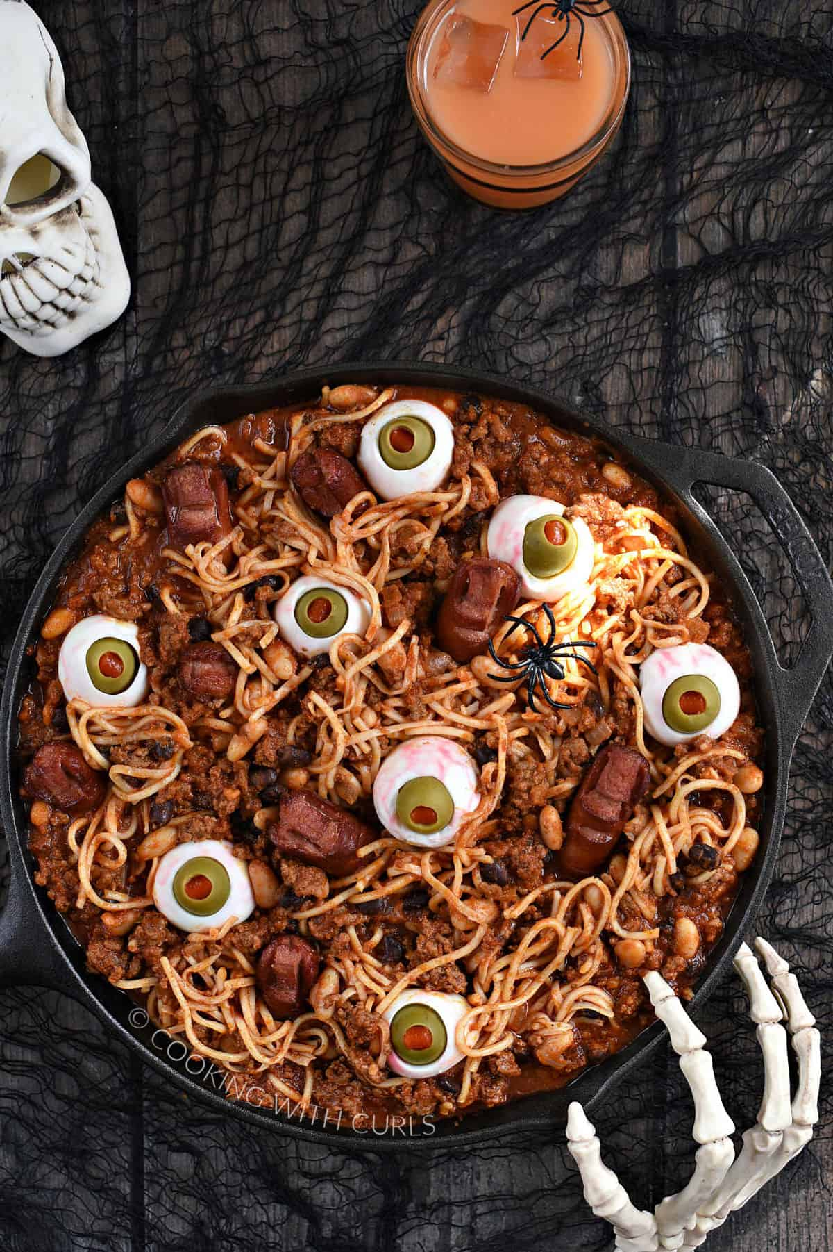 Looking down on a cast iron skillet filled with Chili with noodles, beans, egg eyes, and hot dog fingers and toes.