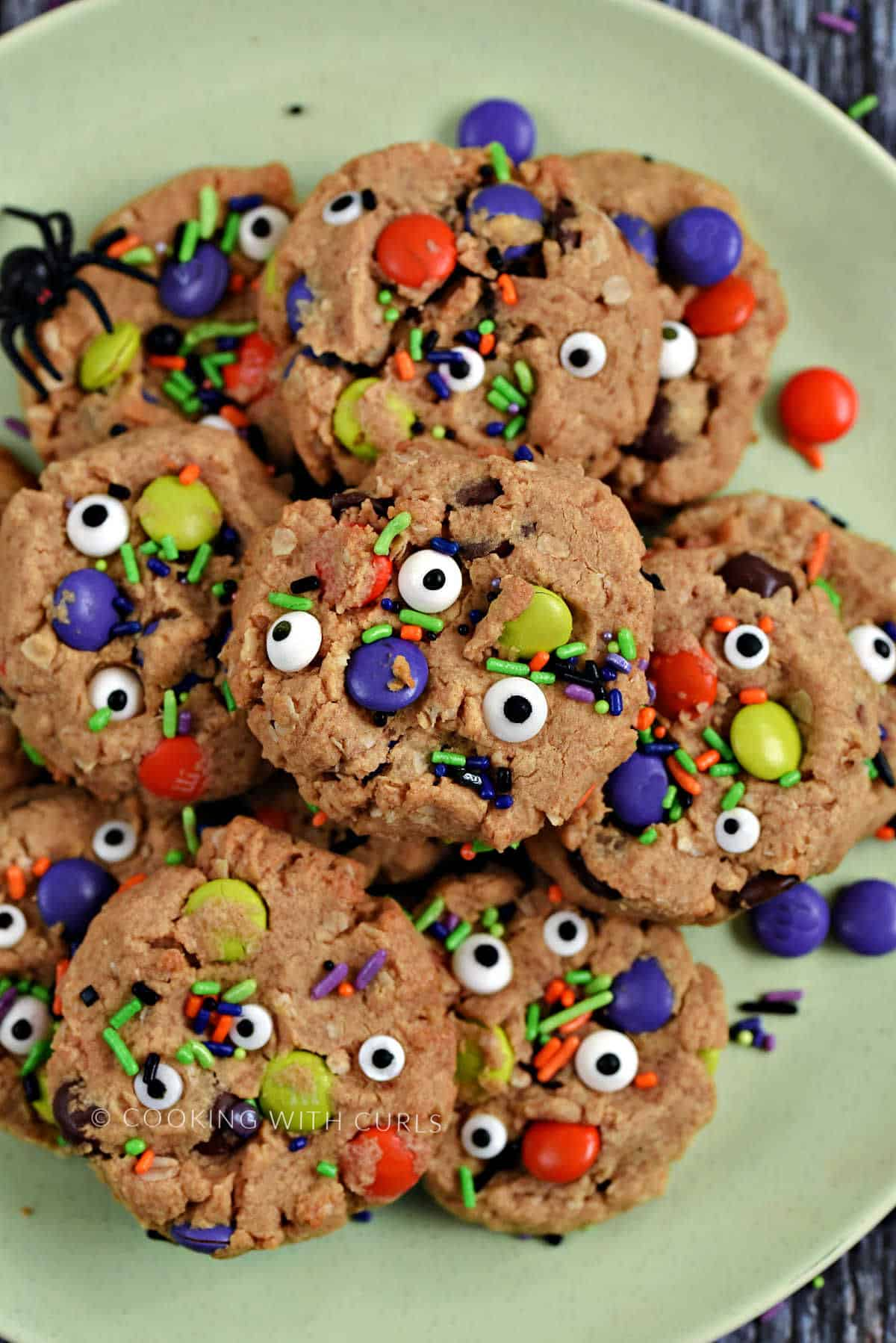 Cookies topped with candy eyes, M&M's, and colorful sprinkles piled up on a green plate.
