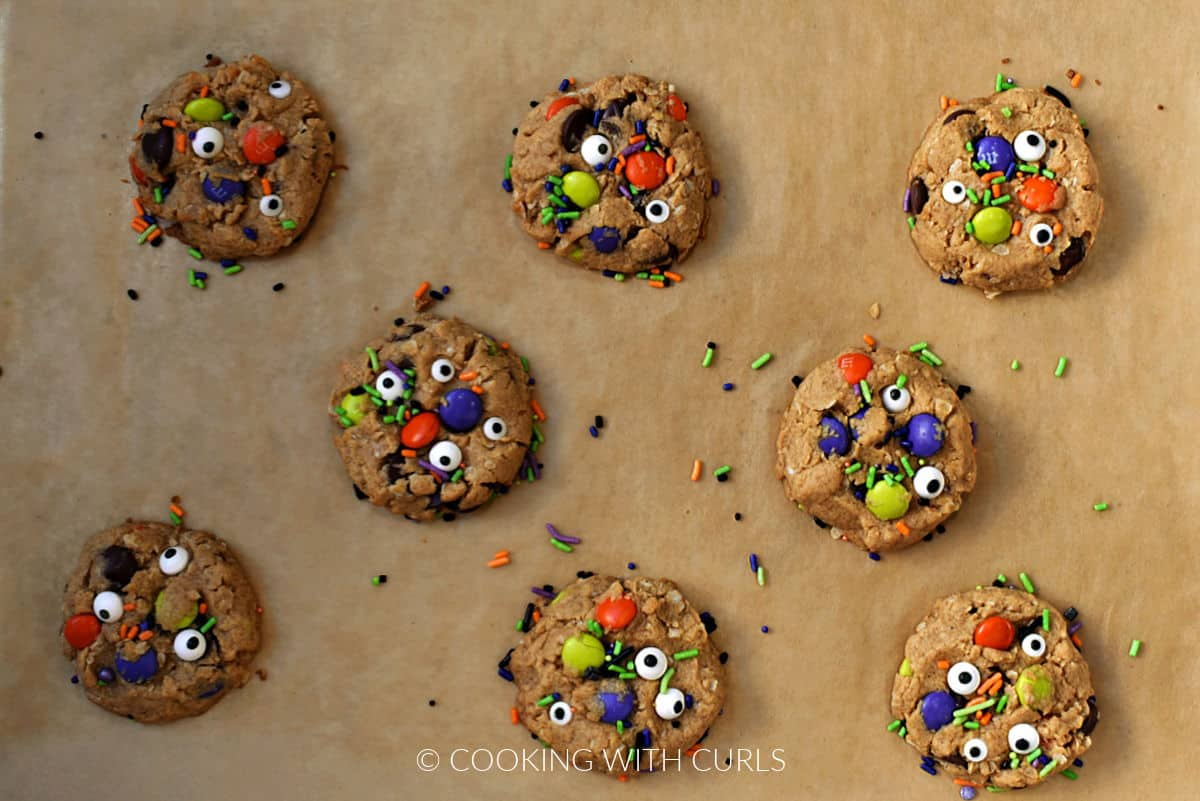 Eight baked monster cookies on a parchment paper lined baking tray.