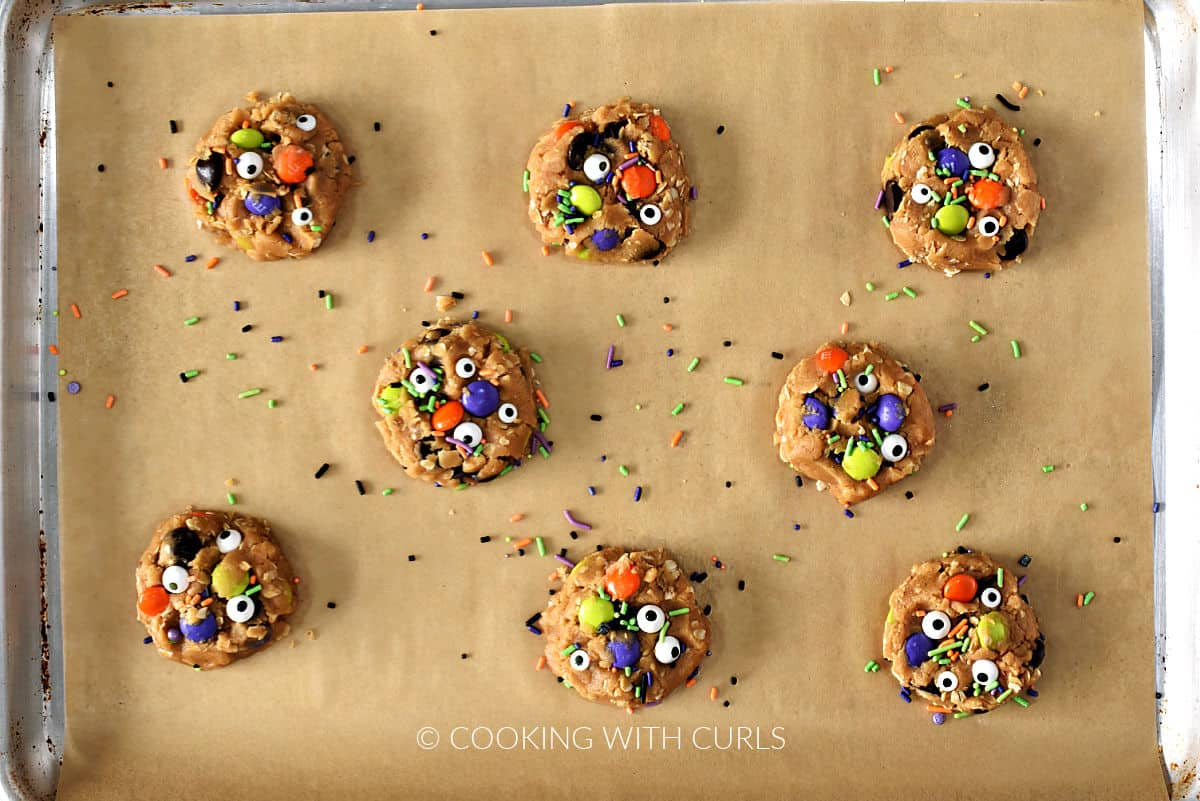 Eight cookie dough balls smashed on a parchment lined baking sheet and sprinkled with candy eyes and colorful jimmies.