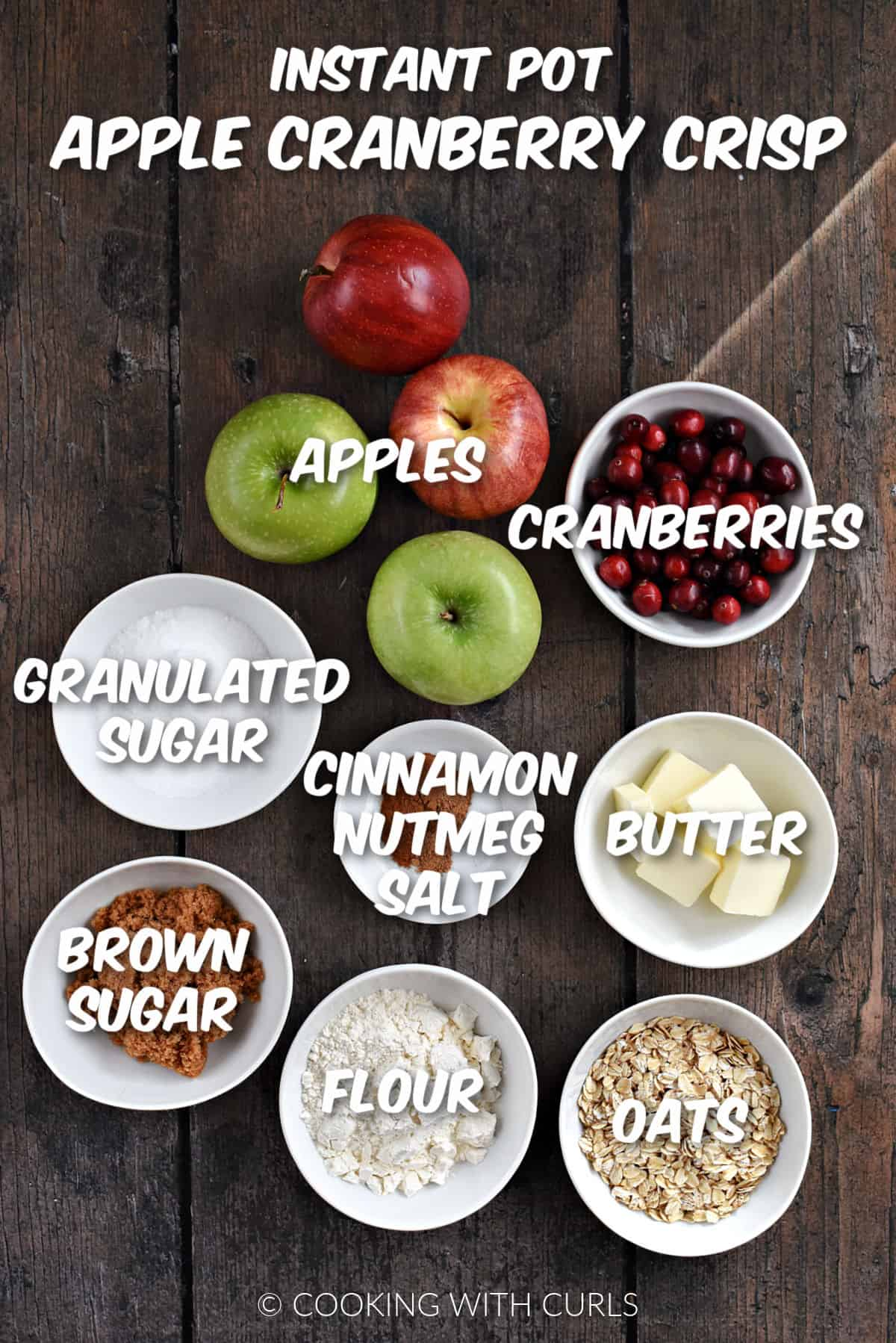 Four apples, cranberries, sugars, butter, flour, oats and seasonings in white bowls.