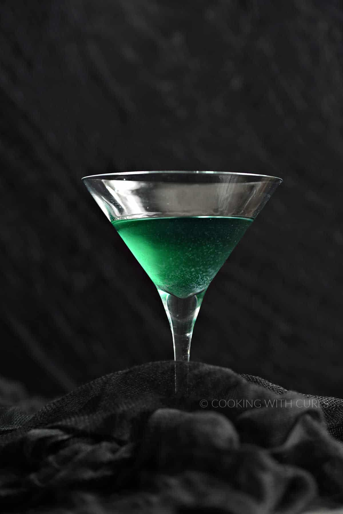 Glittering green cocktail in a martini glass with a black background.