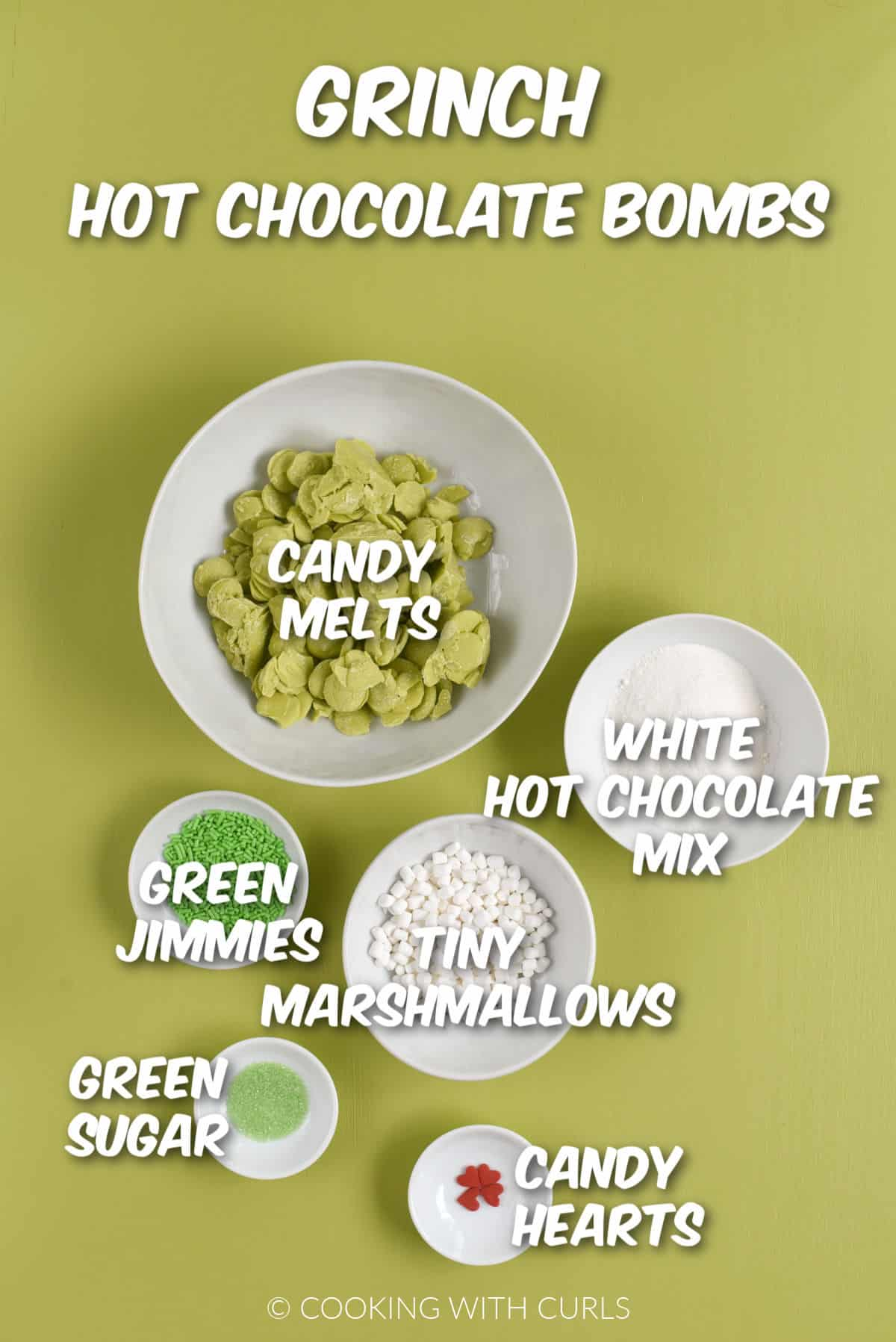 Green candy melts. white hot cocoa mix, tiny marshmallows, red hearts and green sugar in white bowls.