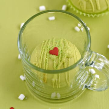 A green chocolate cocoa bomb in a glass mug with a second bomb in the background and tiny marshmallows and red heart candies scattered around the background.