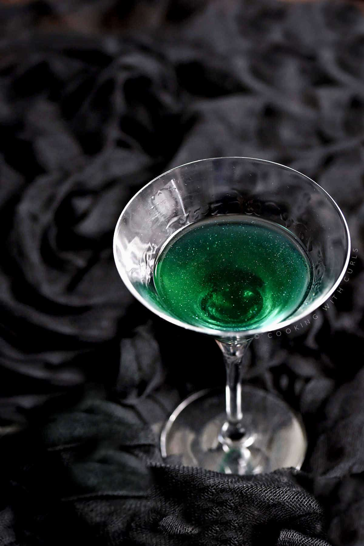 Looking into a green shimmering cocktail in a martini glass.