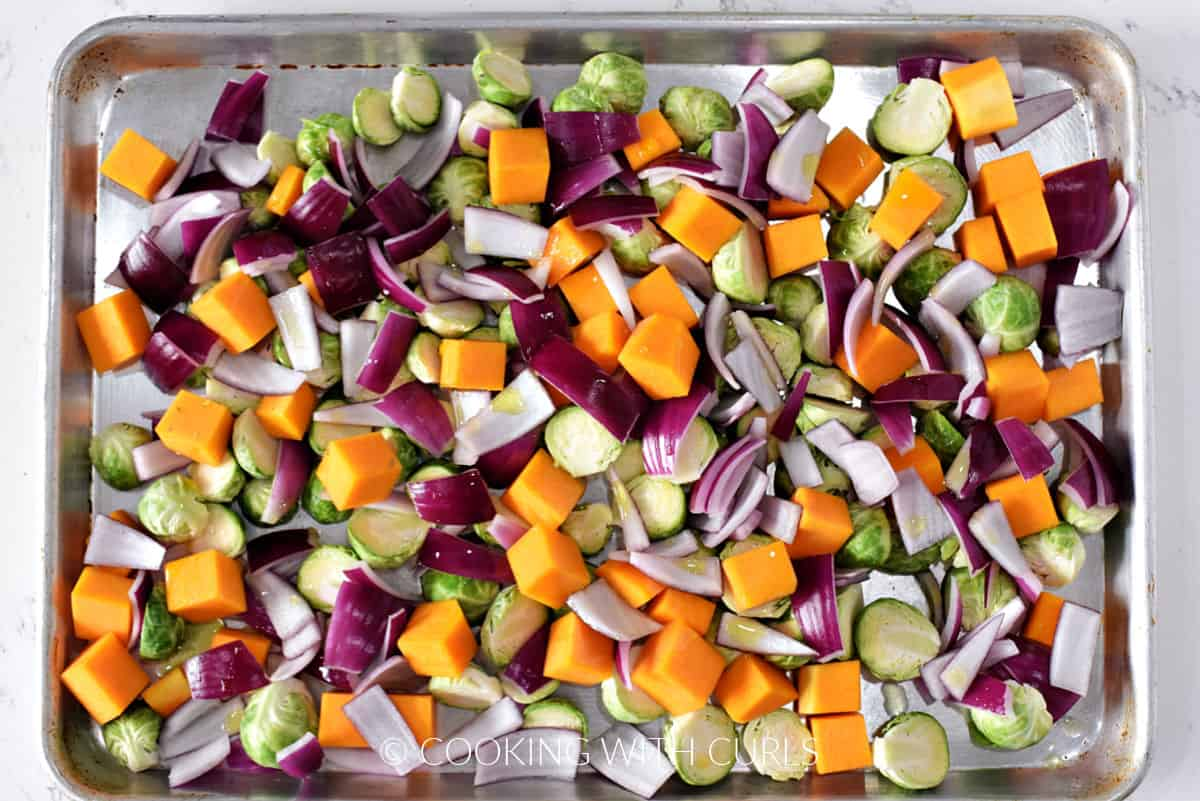 Halved Brussels sprouts, butternut squash chunks, and red onion wedges on a baking sheet.