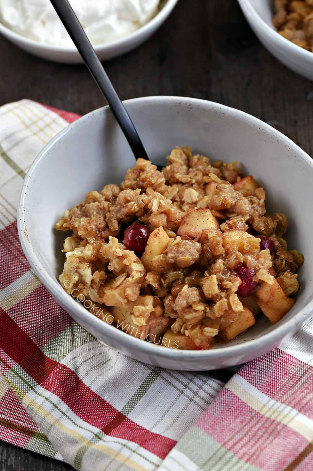 Instant Pot Apple Cranberry Crisp in a small bowl, with a bowl of whipped cream in the background.