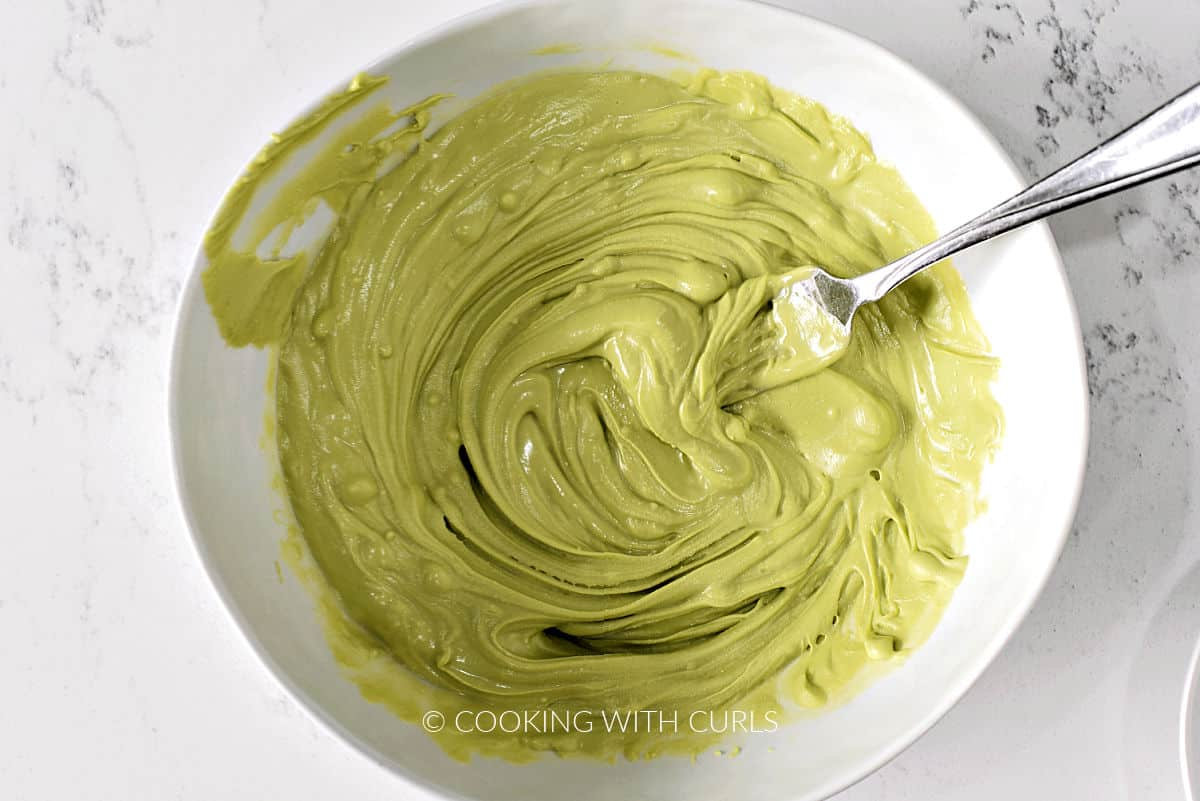Melted green chocolate in a small bowl with a fork.