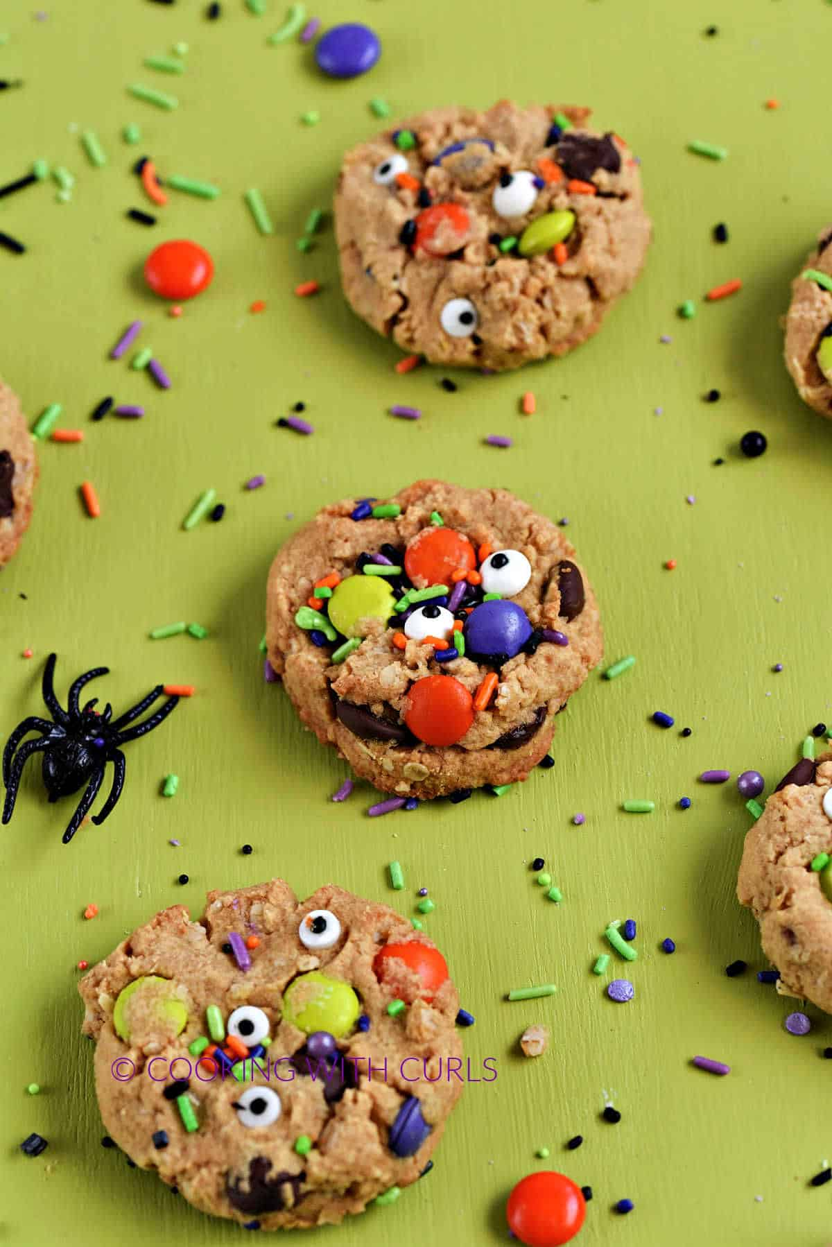 Six cookies with green, orange, and purple M&M's and sprinkles on a green board surrounded by sprinkles.