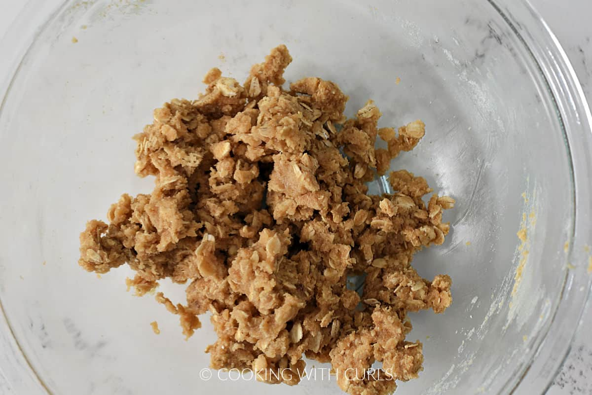 Oats, flour,  brown sugar, and butter mixed together in a bowl.