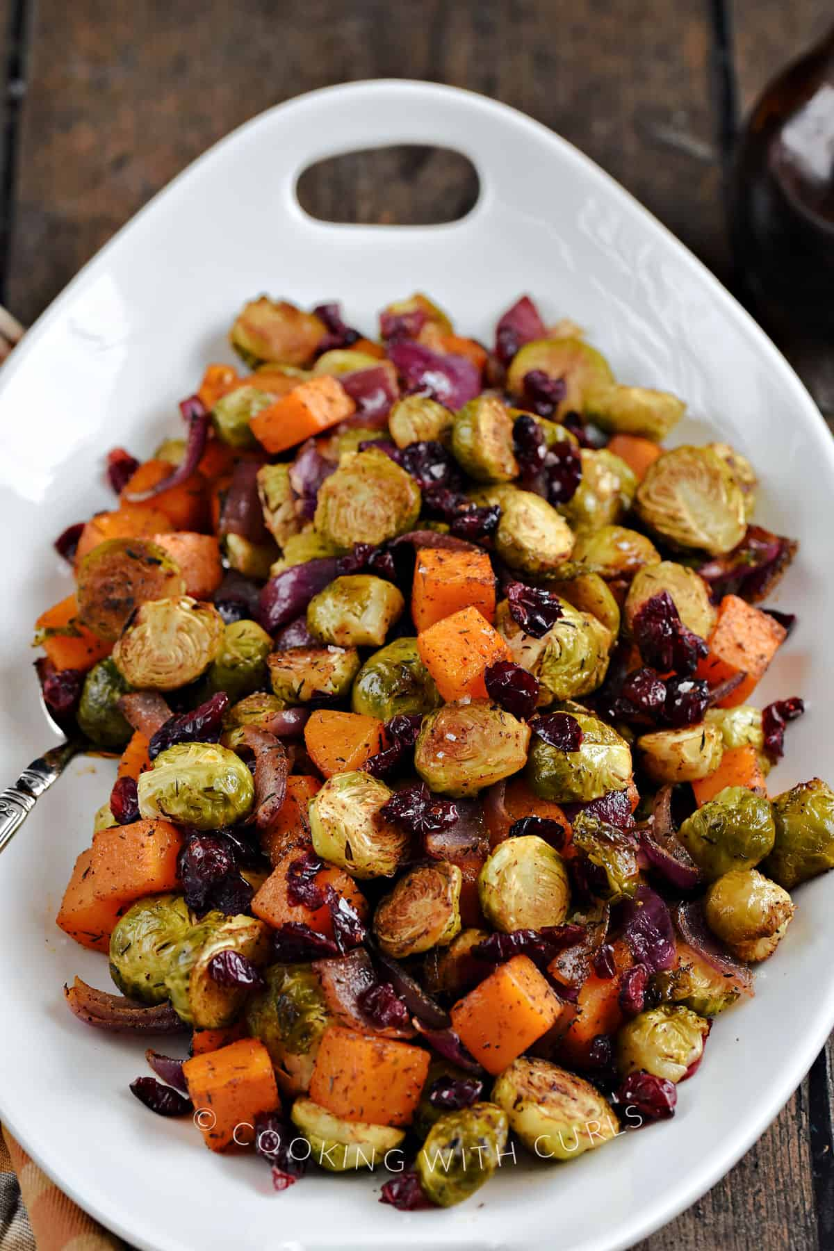 Close-up image of Oven Roasted Brussels Sprouts and Squash with Dried Cranberries in a large platter.