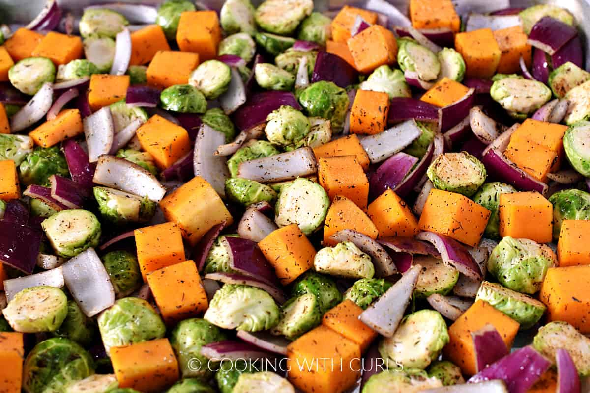 Seasoned Brussels sprouts, squash, and onion on a baking sheet.
