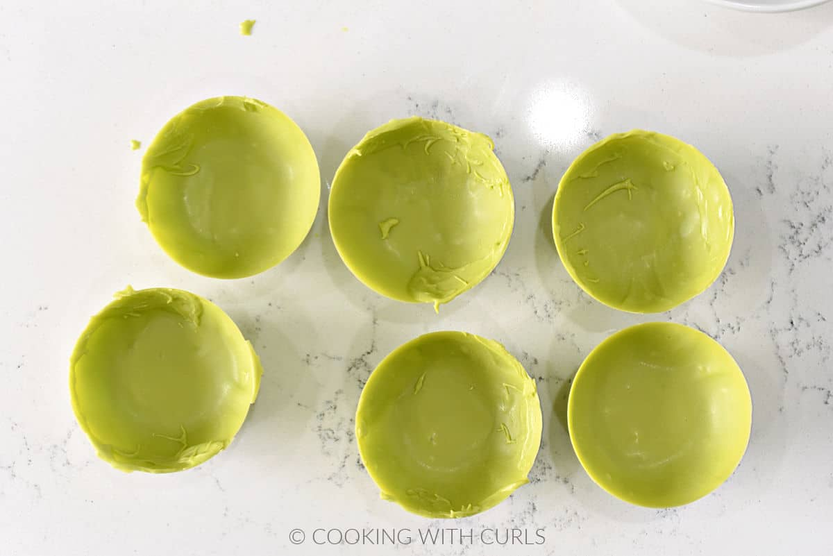 Six green chocolate half circles on a marble background.