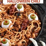 Spooky Halloween Chili with noodles, beans, egg eyes, and hot dog fingers and toes with title graphic across the top.