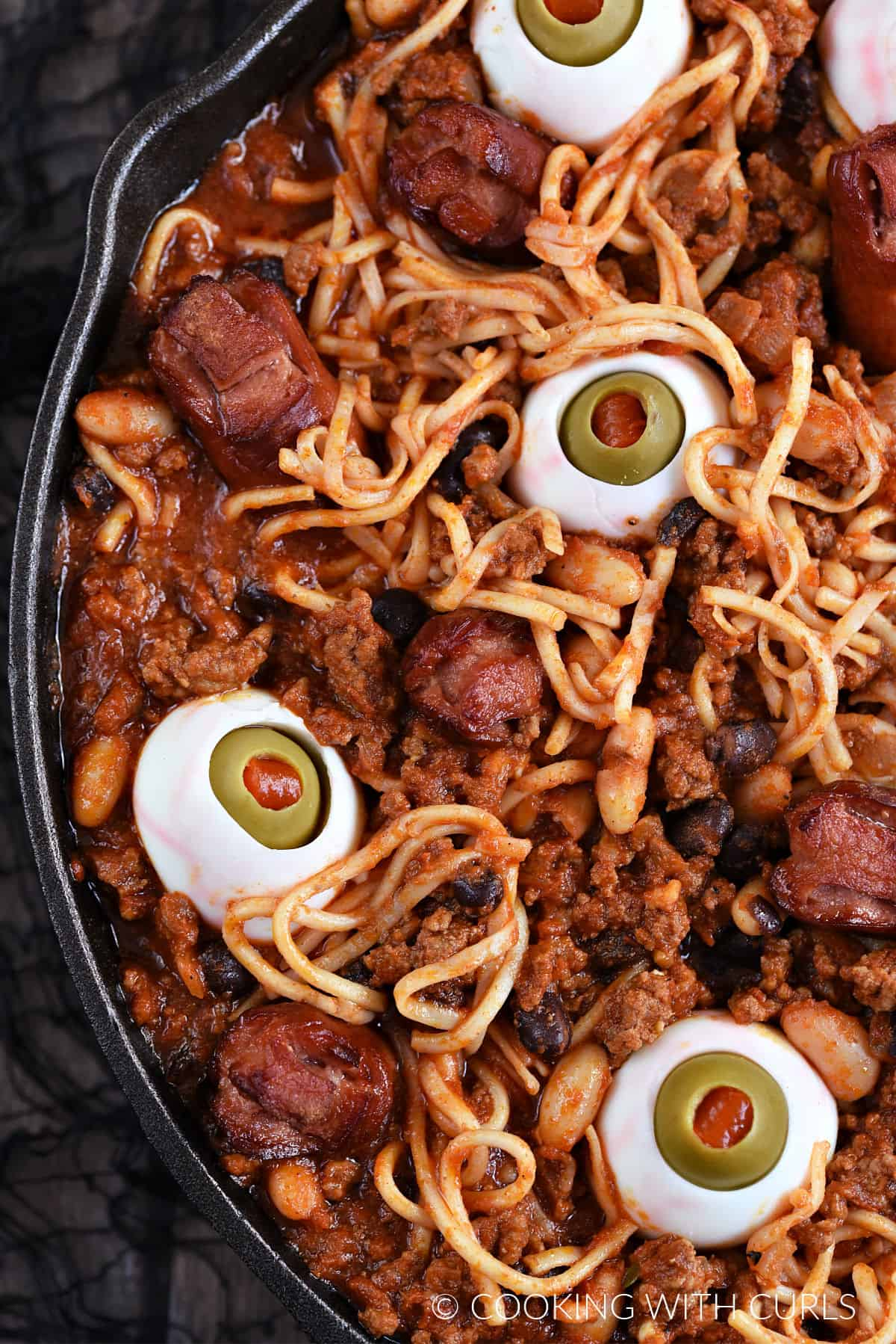 Spooky Halloween Chili with egg eyes, noodle worms, and hot dog fingers and toes in a cast iron skillet..