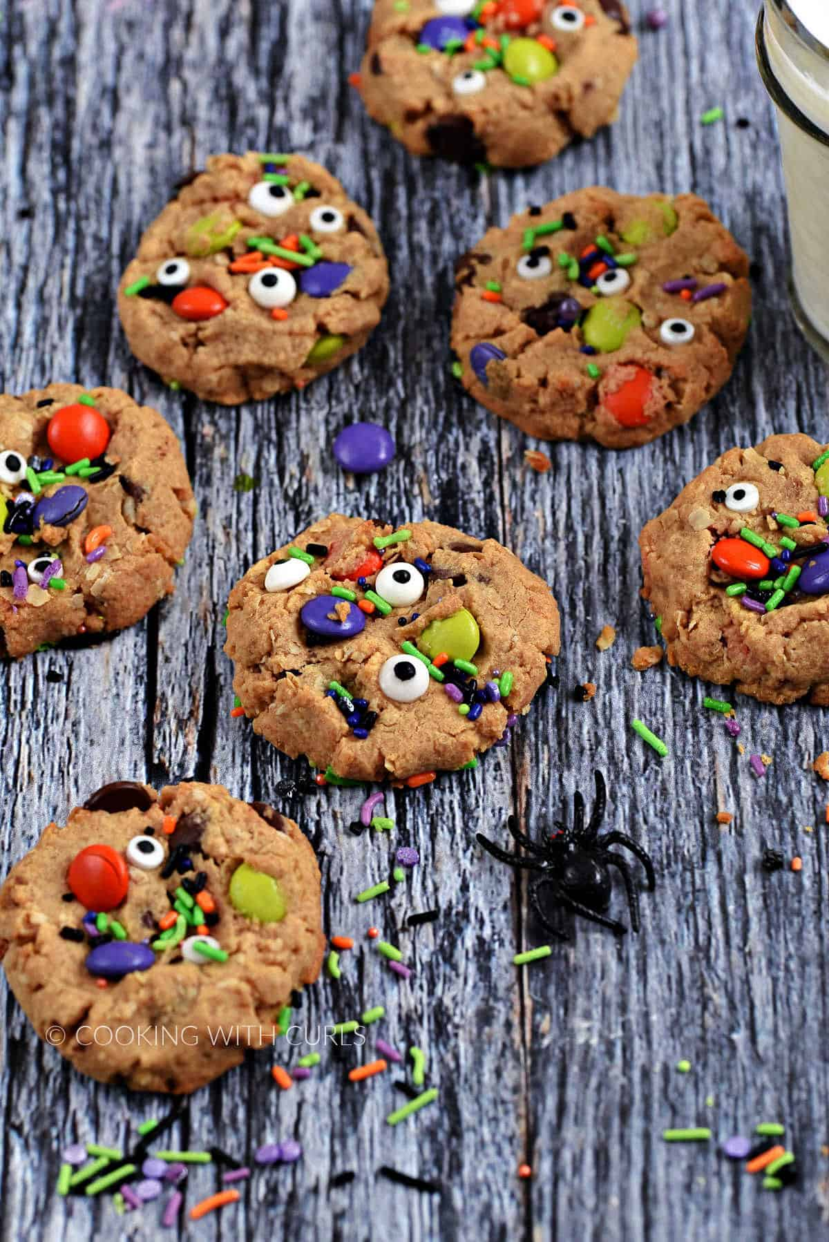 Seven cookies topped with candy eyes, M&M's, and colorful sprinkles surrounded by sprinkles, a black spider, and a glass of milk.