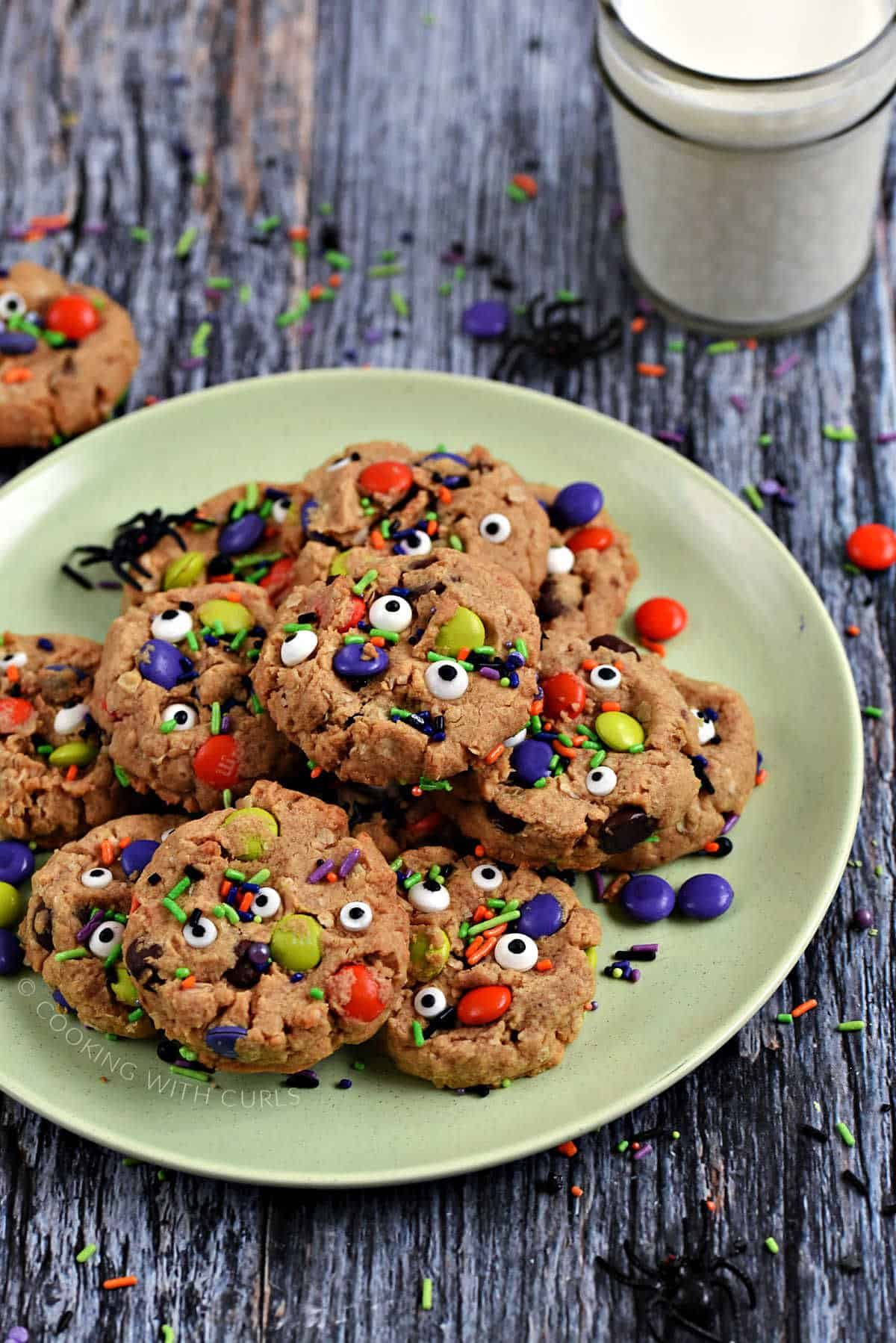 Cookies topped with candy eyes, M&M's, and colorful sprinkles piled up on a green plate surrounded by sprinkles, black spiders, and a glass of milk.