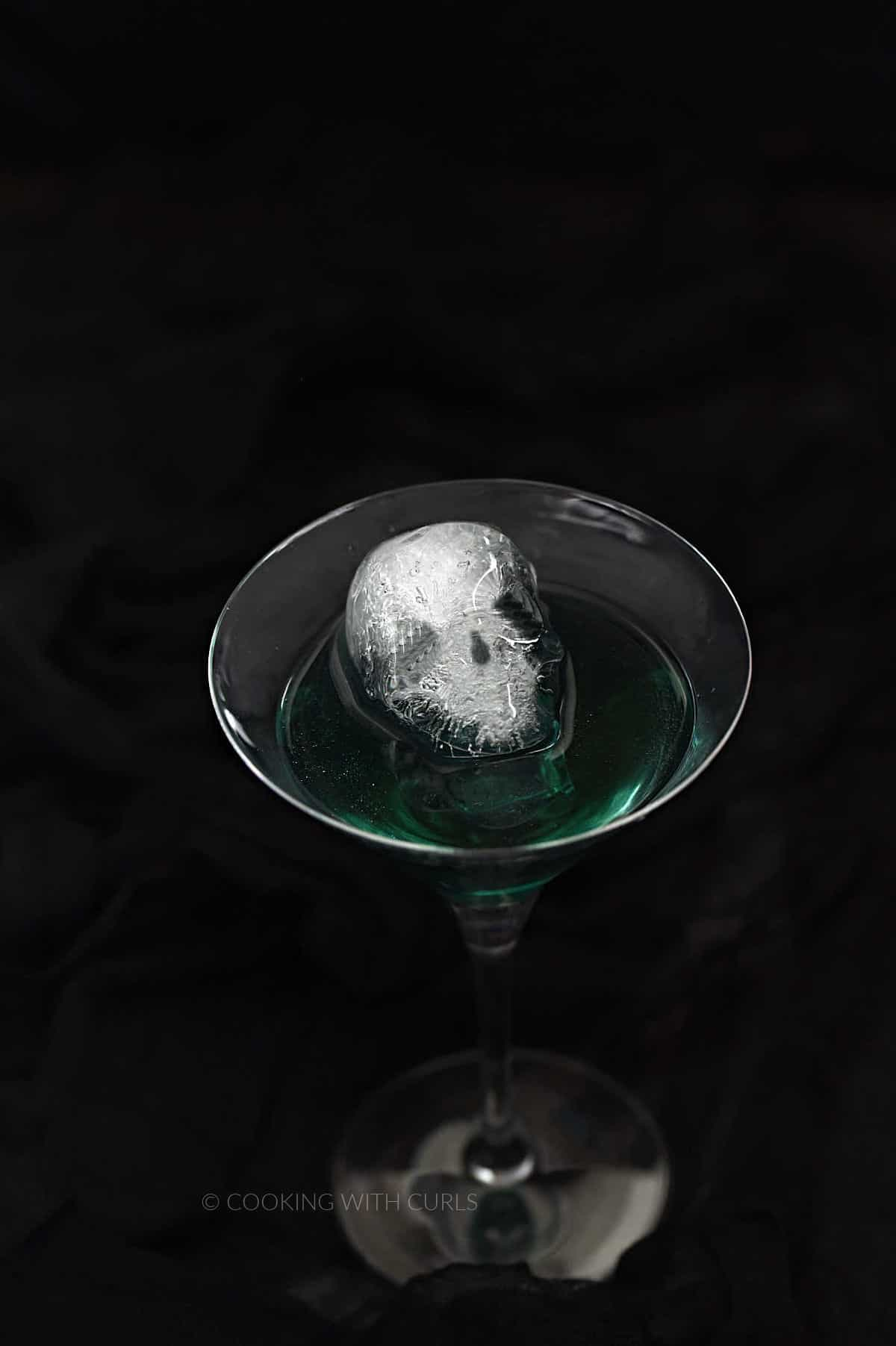 A skull shaped ice cube floating in glittery, emerald green liquid in a martini glass.