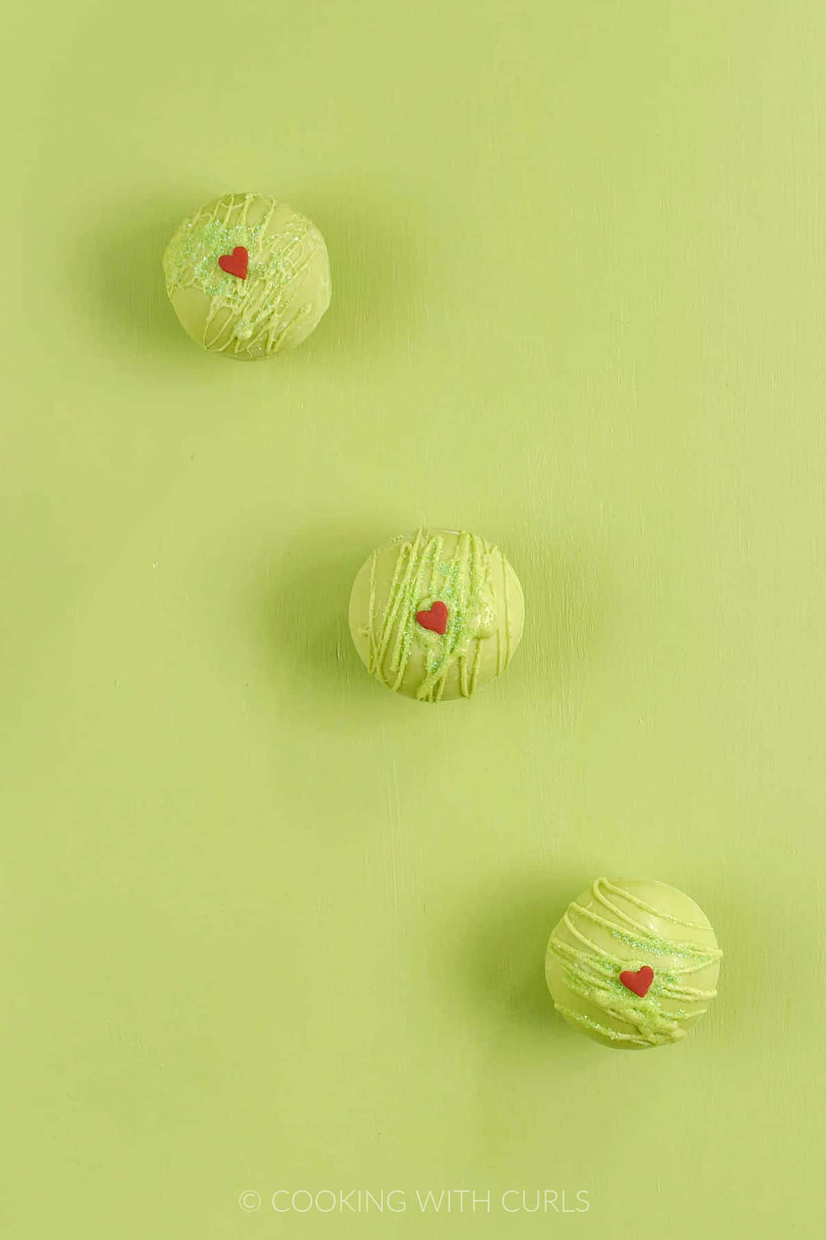 Three Grinch Hot Chocolate Bombs on a green background.